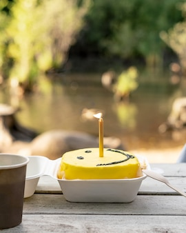 Bento-kuchen mit brennendem kerzenkaffee auf der bank
