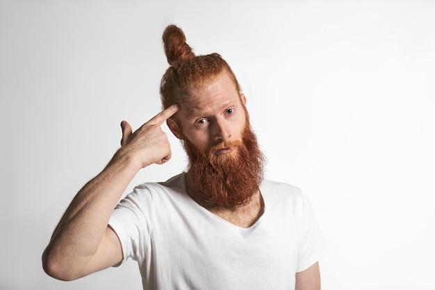 Benutze dein gehirn. porträt des emotionalen empörten männlichen männlichen hipsters mit getrimmtem stilvollem bart und haarknoten, die an der weißen studiowand aufwerfen, zeigefinger an seiner schläfe drehen, verwirrten blick haben