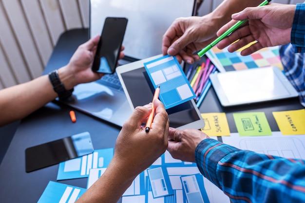 Benutzererfahrung teamwork mobile ux / ui designer, die im arbeitsraum mitarbeiten.