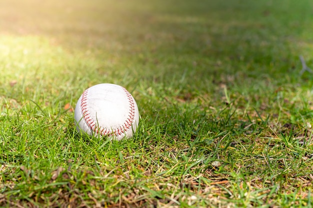 Benutzter baseball, der auf grünes gras legt