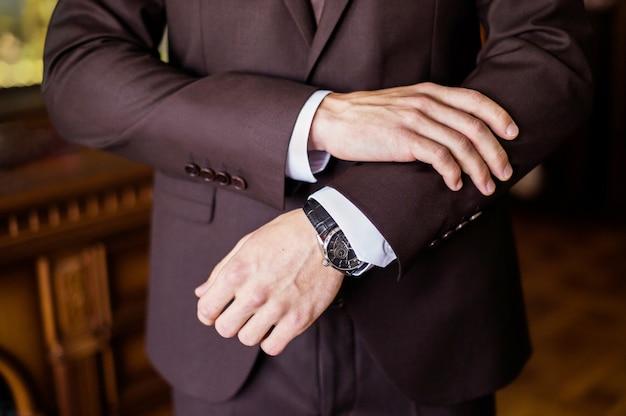 Beobachten sie die hand eines mannes, die gebühren des bräutigams, die hochzeitsvorbereitung, die vorbereitung auf die arbeit, stellen sie die uhr auf den zeiger, befestigen sie die uhrzeit, den stil des mannes, den sinn für stil, der die ärmel korrigiert