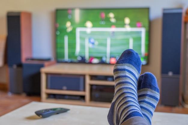 Beobachten sie ein fußballspiel im fernsehen mit den füßen auf dem tisch, auf dem sich die fernbedienung befindet