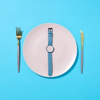 Beobachten sie mit der zeit sechs uhr auf einem weißen teller mit messer und gabel an einer blauen wand, platz für text. konzept der begrenzung der nahrungsaufnahme und gewichtsverlust. flach liegen.