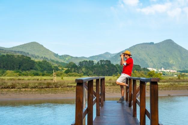 Beobachten sie vögel mit einem fernrohr von den holzpfeilern der urdaibai-sümpfe, einem biosphärenreservat in bizkaia neben mundaka. baskenland
