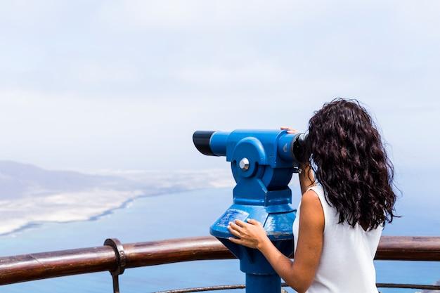 Beobachtender fernglas-teleskop des hipster-touristenblickes auf panoramablick, lebensstilkonzeptreise, reisender auf hintergrundberg und blauem seelandschaftshorizont, wanderer des jungen mädchens, das hände zeigt
