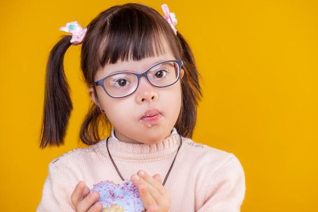 Beobachtung ihrer donuts. neugieriges hübsches kind mit chromosomenanomalie, das überall auf ihrem gesicht zerbröckelt