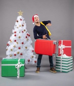 Beobachtung junger mann mit rotem koffer auf grau isoliert