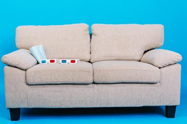Bequeme couch mit 3d-brille, popcorn lokalisiert auf blauem hintergrund. vorbereitung zum ansehen von filmen, entspannung, genießen des kinos zu hause