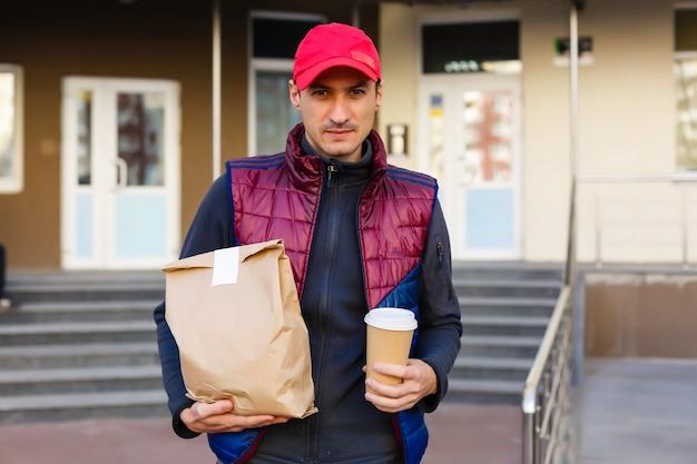 Bequeme lieferung von speisen nach hause. blick auf einen glücklichen kurier, der lebensmittel aus dem supermarkt liefert.