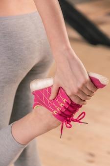 Bequeme turnschuhe. sportlerin mit bequemen rosa turnschuhen, die sich nach dem training die beine strecken