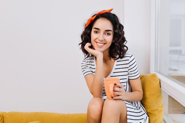 Bequeme zeit zu hause mit tasse tee der jungen erstaunlichen frau im kleid, das auf sofa nahe fenster in der modernen wohnung entspannt. glück, freude, entspannung, modisch, lächeln