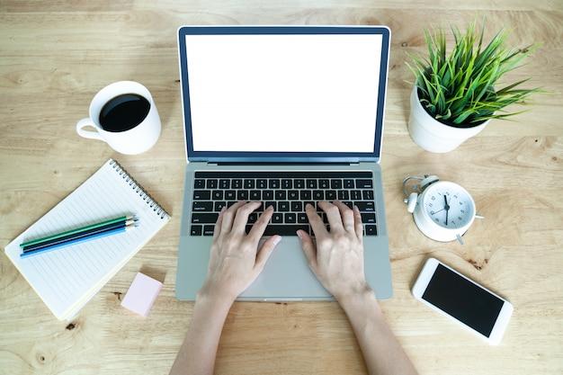 Bequemer arbeitsplatz mit kaffeetasse des laptops und baumtopf auf holztisch. draufsicht bürotisch schreibtisch. , schreibtisch aus holz mit mobiler buchnotiz und uhr