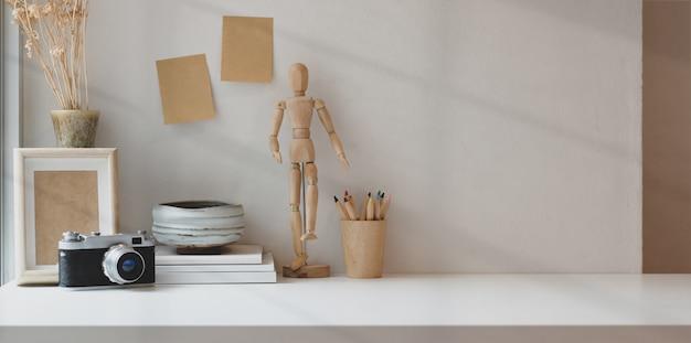 Bequemer arbeitsplatz mit kopienraum mit fotografbürozubehör