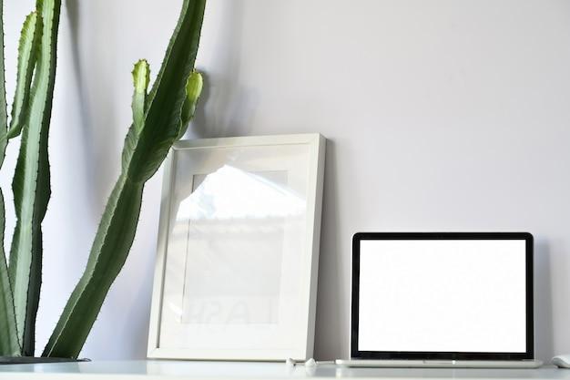 Bequemer arbeitsplatz mit laptop-computer des leeren bildschirms und modellplakat auf weißem schreibtischbürotisch