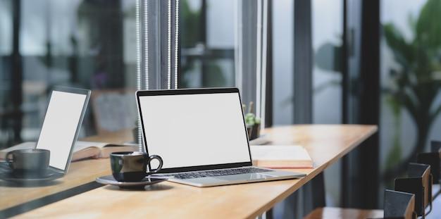 Bequemer arbeitsplatz mit offener laptop-computer des leeren bildschirms auf holztisch