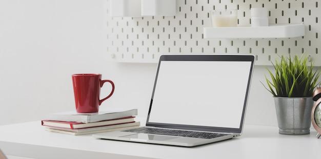 Bequemer arbeitsplatz mit offener laptop-computer des leeren bildschirms mit roter kaffeetasse und büroartikeln
