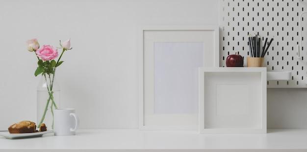 Bequemer arbeitsplatz mit verspotten herauf rahmen- und kopienraum auf weißer tabelle und weißer wand