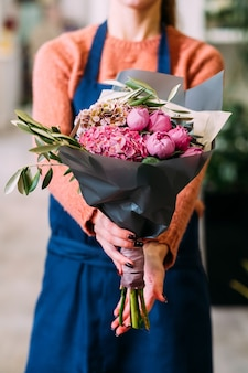 Bequemer blumenstraußversand für jemanden, den sie lieben. frauenhände, die eine kreative anordnung von pfingstrosen und hortensien halten