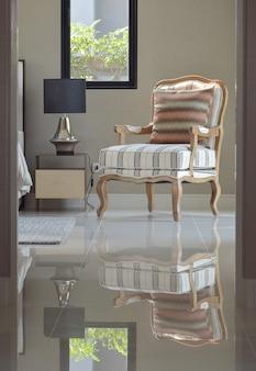 Bequemer klassischer lounge-sessel neben dem nachttisch