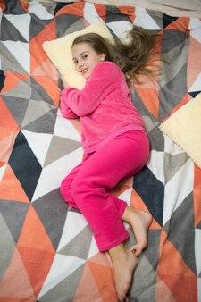 Bequemer schlafanzug zum entspannen. kleines kind des mädchens trägt weiche, süße pyjamas, während es sich auf dem bett entspannt. verspieltes baby entspannend. pyjamas und kleidung für zu hause. pyjamas und schlafzimmertextilien. kinder genießen freizeit.