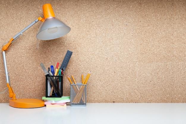 Bequemer schreibtisch mit lampe und ausstattung für studenten oder büro mit korkplatte
