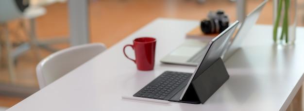 Bequemer schreibtisch mit laptop, digitalem tablet, becher, kamera, büromaterial und dekoration