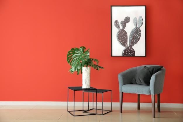 Bequemer sessel und tropische blätter auf tisch nahe farbwand im raum