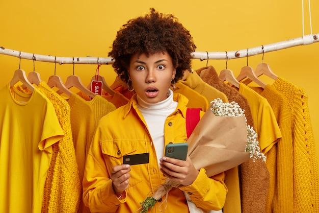 Bequemes banking- und online-shopping-konzept. die verblüffte junge afroamerikanerin hat einen schockierten blick in die kamera geworfen, hält handy und blumenstrauß, gelbe kleidung auf kleiderbügeln im hintergrund