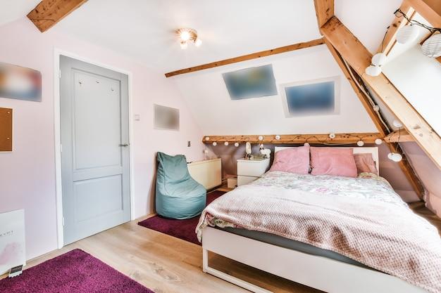 Bequemes bett mit kissen und decke in der nähe von stuhl und fernseher gegen fenster mit vorhängen im hellen dachgeschoss schlafzimmer zu hause
