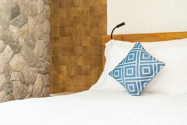 Bequemes blaues kissen auf weißer bettdekoration im schlafzimmer