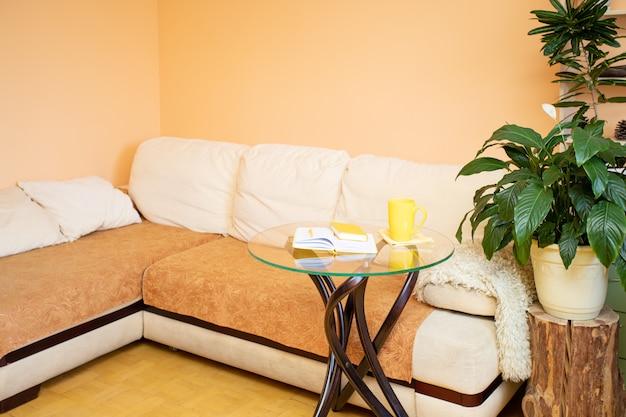 Bequemes großes ecksofa, gewächshauspflanzen und kreativer glastisch und holzstumpf. zuhause wirklich gemütliches interieur zur entspannung.