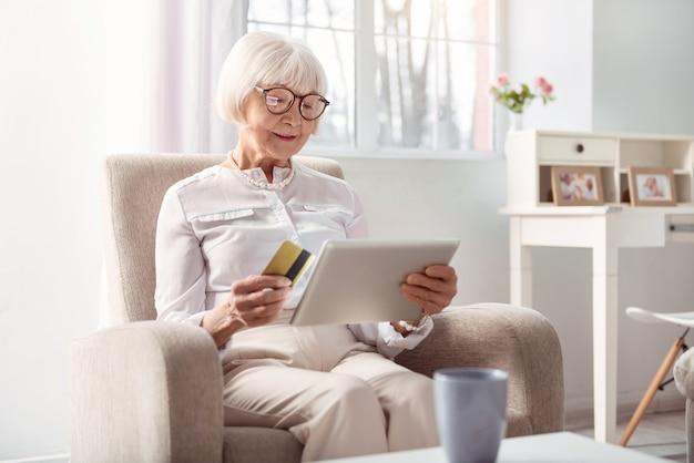 Bequemlichkeit genießen. charmante ältere dame, die im sessel im wohnzimmer sitzt und mit ihrer bankkarte für einen online-kauf bezahlt