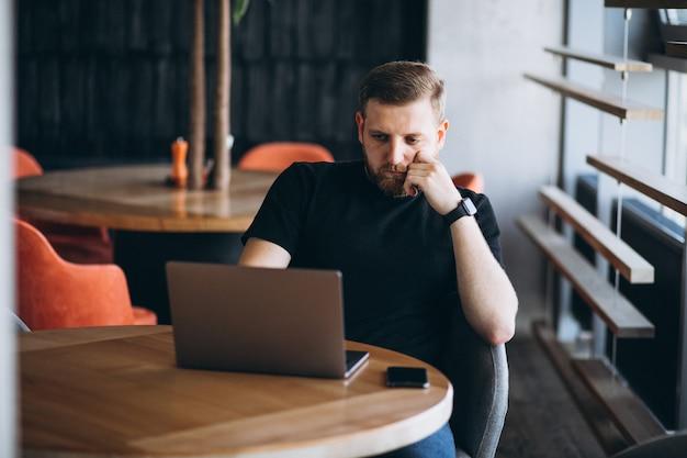 Beraded mann, der an laptop in einem café arbeitet