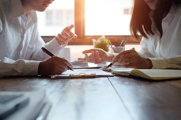 Beraten sie die geschäftsleute, die finanzdaten auf holztisch und morgenlicht treffen und planen.