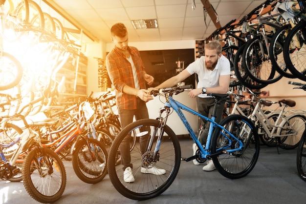 Berater zeigt dem kunden fahrrad im sportgeschäft