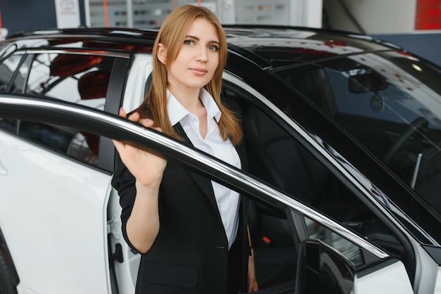Beraterin der jungen frau im ausstellungsraum, der nahe auto steht