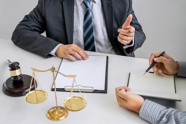 Beratung eines männlichen anwalts und eines professionellen geschäftsmannes, der in einer anwaltskanzlei arbeitet und diskutiert. richter hammer mit waage der gerechtigkeit.