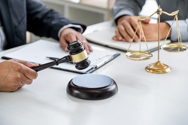 Beratung eines männlichen anwalts und eines professionellen geschäftsmannes, der in einer anwaltskanzlei arbeitet und diskutiert. richter hammer und waage der gerechtigkeit.