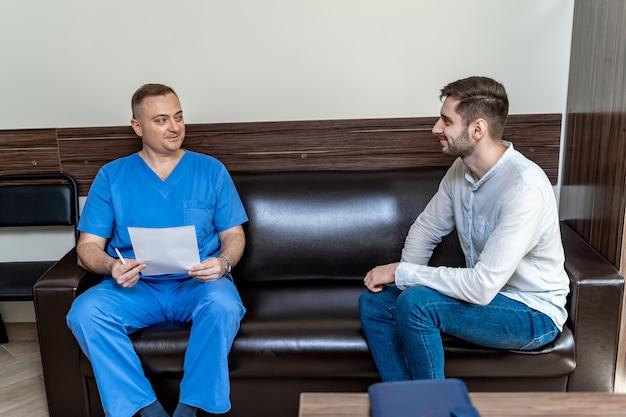 Beratung in der klinik. arzt und männlicher patient sitzen auf dem sofa im büro.