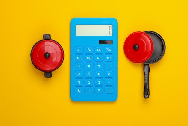 Berechnung der kochkosten. taschenrechner und spielzeugpfannen auf gelbem grund. draufsicht. minimalismus