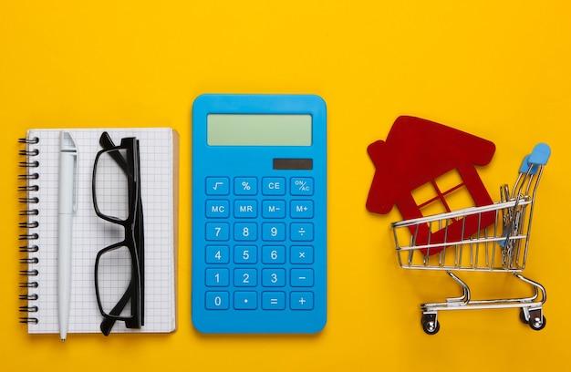 Berechnung der kosten für den kauf oder verkauf eines hauses. rechner, figur eines hauses in einem einkaufswagen, notizbuch auf gelb. flach liegen