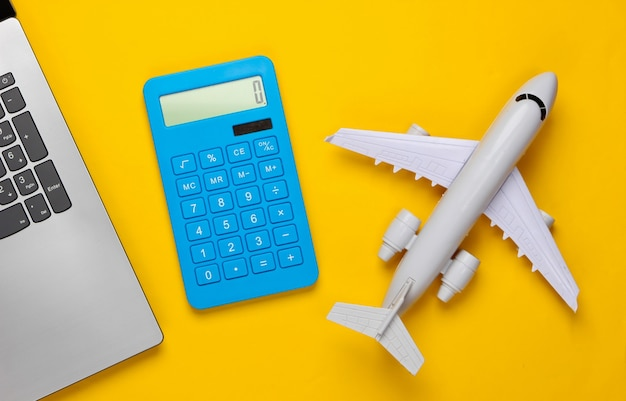 Berechnung der kosten für tourismus oder auswanderung. online-buchung. laptop, flugzeug, taschenrechner auf gelb