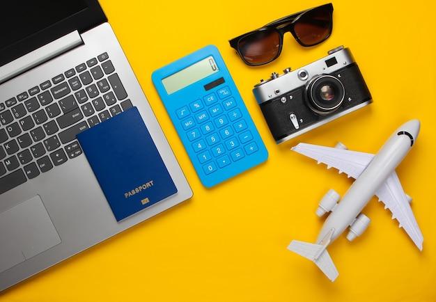 Berechnung der kosten für tourismus oder auswanderung. online-buchung. laptop, flugzeug, taschenrechner, reisepass und sonnenbrille auf einem gelben