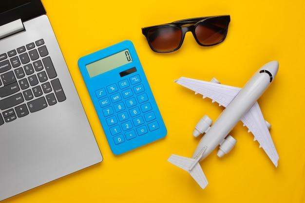 Berechnung der kosten für tourismus oder auswanderung. online-buchung. laptop, flugzeug, taschenrechner und sonnenbrille auf einem gelben
