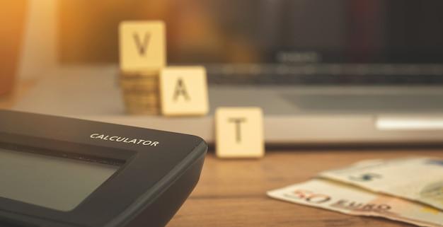 Berechnung der mehrwertsteuer in europa, banner mit mehrwertsteuerwort und taschenrechner auf dem business-desktop mit laptop
