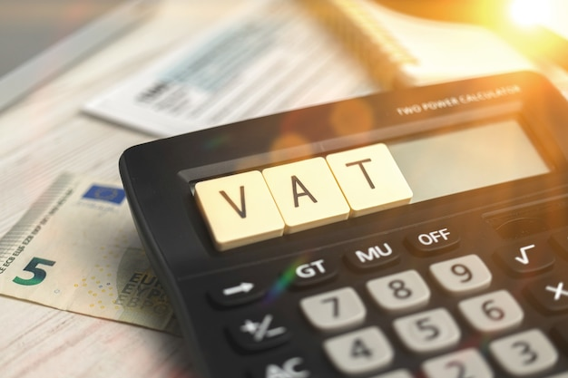 Berechnung der mehrwertsteuer. mehrwertsteuerwort auf holzblock und taschenrechner auf dem geschäftsdesktop