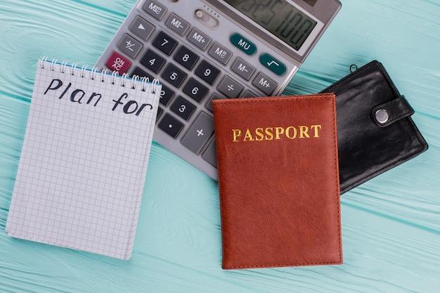 Berechnung der tourismuskosten. reisepass, taschenrechner, geldbörse auf blauem hintergrund. draufsicht flach.