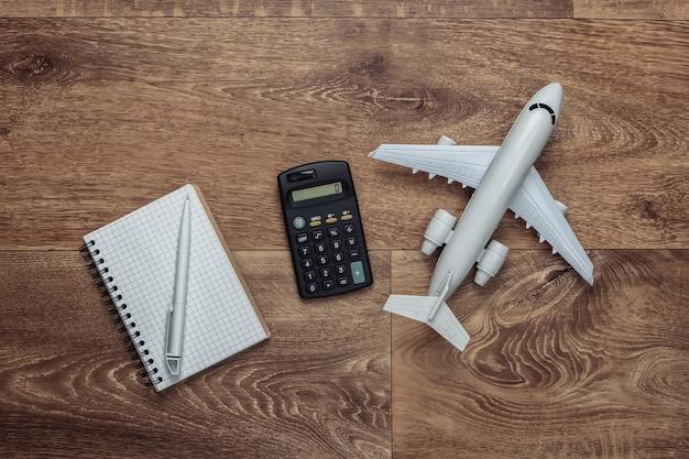 Berechnung der urlaubskosten. flugzeugfigur, taschenrechner und notizbuch auf holzboden. flach legen