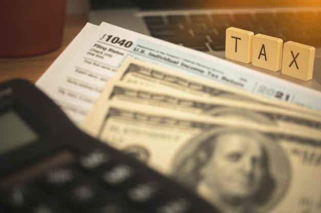 Berechnung des steuerberichts. bereiten sie sich auf das konzept der steuersenkung vor. 1040 steuerantragsformular, taschenrechner und dollarnoten auf dem business-desktop