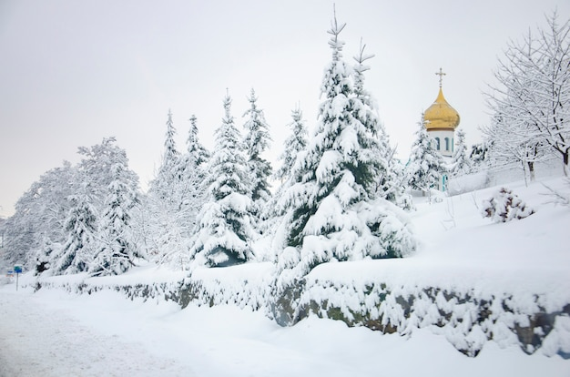 Bereifter schneebedeckter gezierter baum und eine kirche mit goldener haube in den karpatenbergen, ukraine
